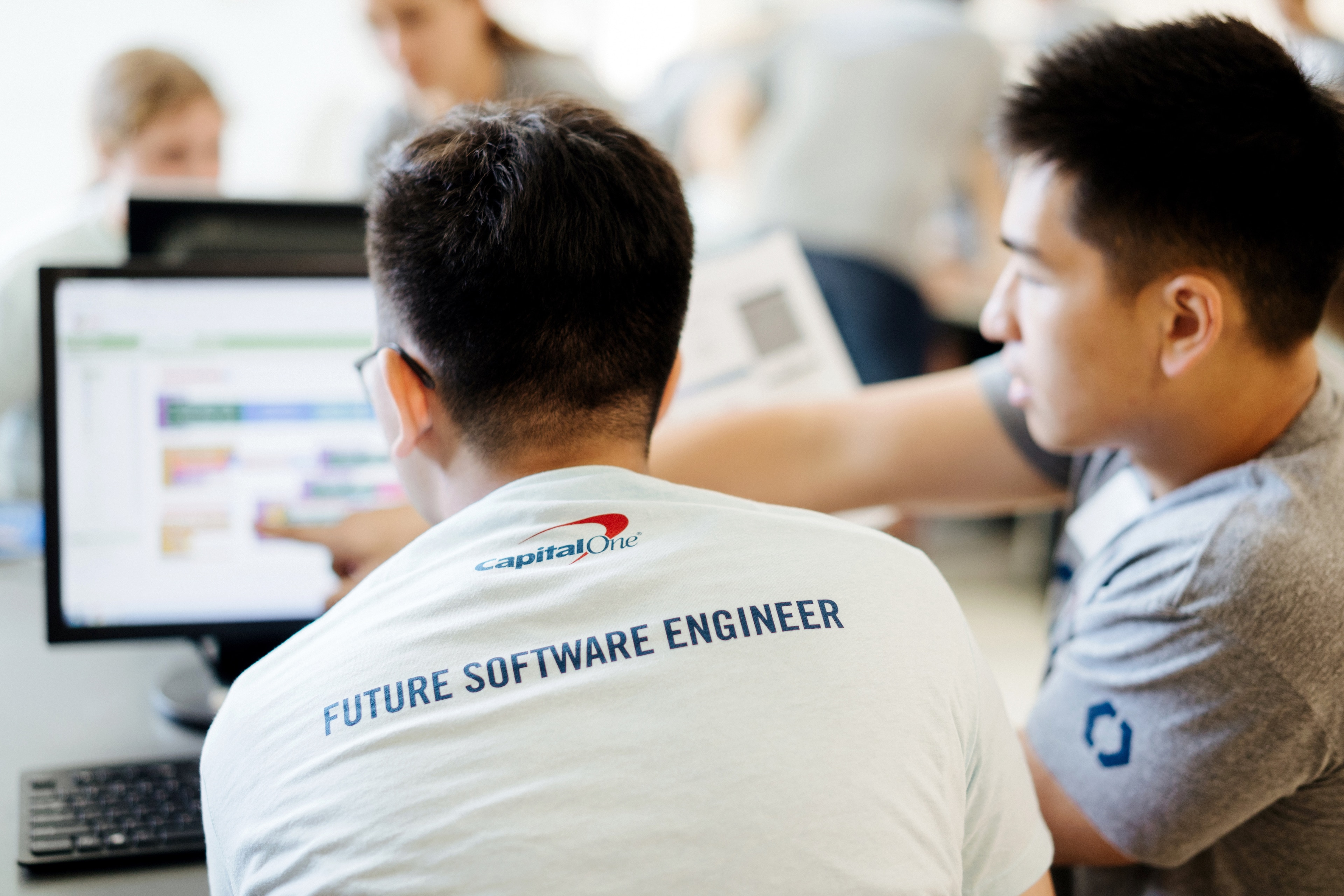 """A student and Capital One technologist sit facing a computer. The back of the student's shirt reads """"Future Software Engineer"""""""